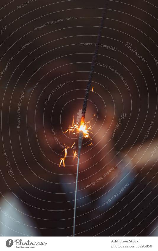 Wunderkerze gegen verschwommene Person in der Natur Brandwunde ausstoßen Landschaft Funken Feuer Pyrotechnik festlich Veranstaltung glühen schimmern Glanz