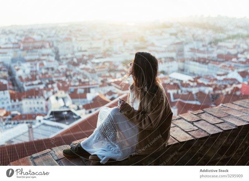 Verträumte Frau sitzt an der Grenze nahe der Stadt Morgen Borte sitzen ruhen sonnig jung verträumt bewundern Portugal Stadtbild Großstadt Wochenende Barriere