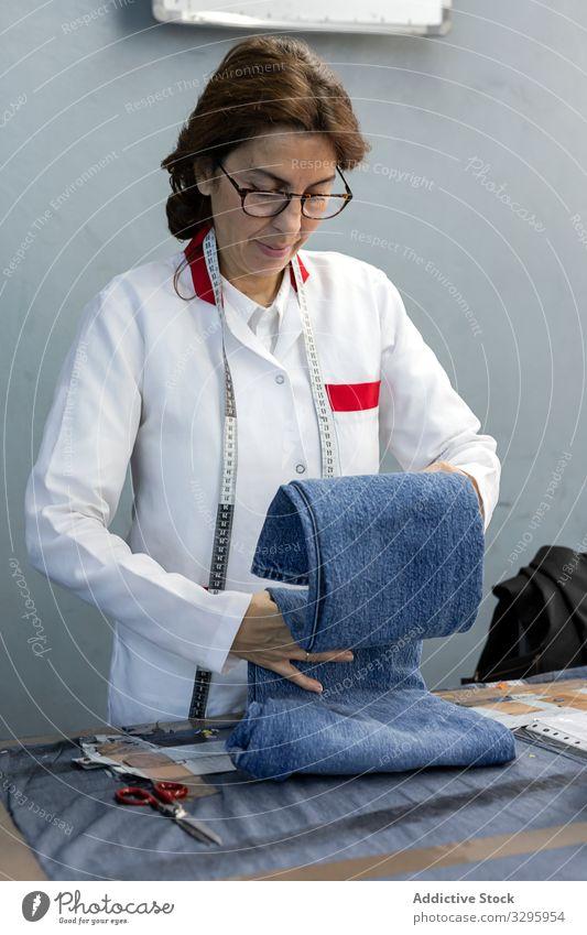 Arbeitende Frau bei der Kontrolle von Textilfabriken Industrie Fabrik Bekleidung Herstellung Arbeiter Maschine Nähen Hände Gewebe Hose Blue Jeans Beruf