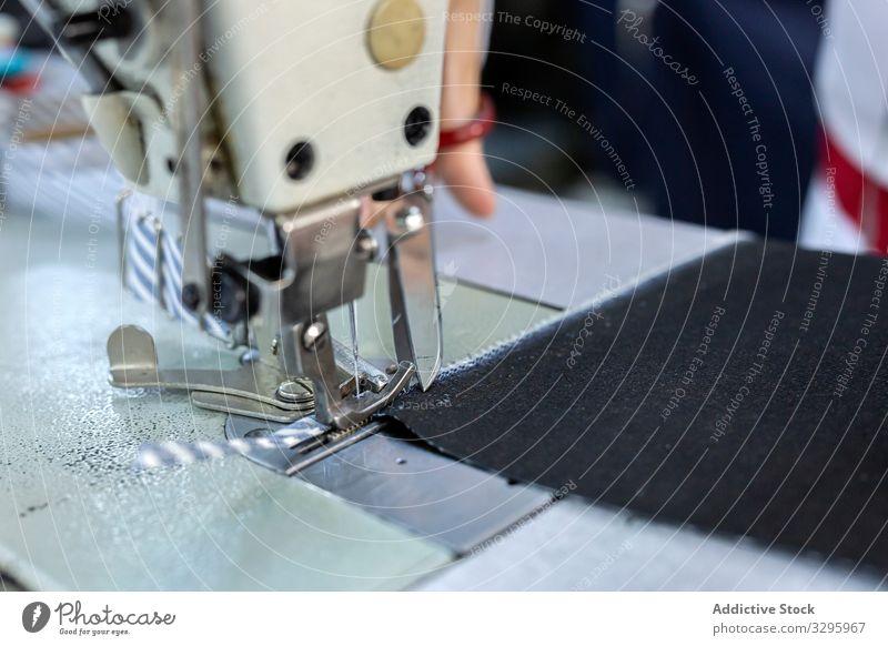 Frauenhände in einer Textilfabrik beim Nähen auf einer Industrienähmaschine. Fabrik Bekleidung Herstellung Arbeiter Maschine Hände Gewebe Hose Blue Jeans Beruf