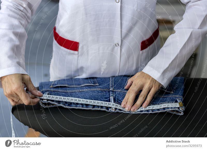Frauenhände in einer Textilfabrik beim Bügeln auf einer Industrienähmaschine. bügelnd Fabrik Bekleidung Herstellung Arbeiter Maschine Nähen Hände Gewebe Hose