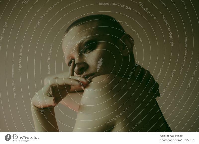Sexy nackte Frau mit Glatze in dunklem Studio erotisch provokant kahl rasierter Kopf jung sexy sitzen Körper Dessous schlank Boudoir BH sich[Akk] ausziehen