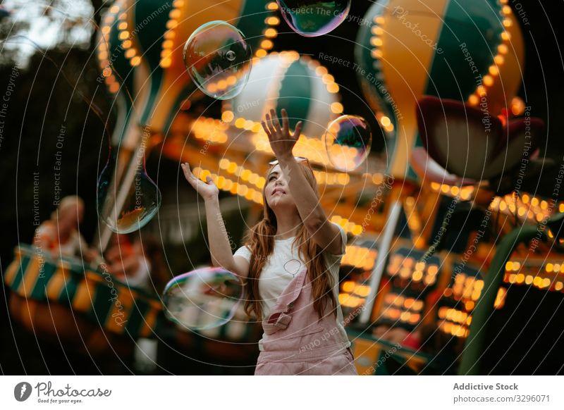 Teenagerin spielt mit Seifenblasen im Vergnügungspark Frau spielen Mädchen Spaß sorgenfrei spielerisch genießen Stil Mode trendy modisch rein kindlich jung