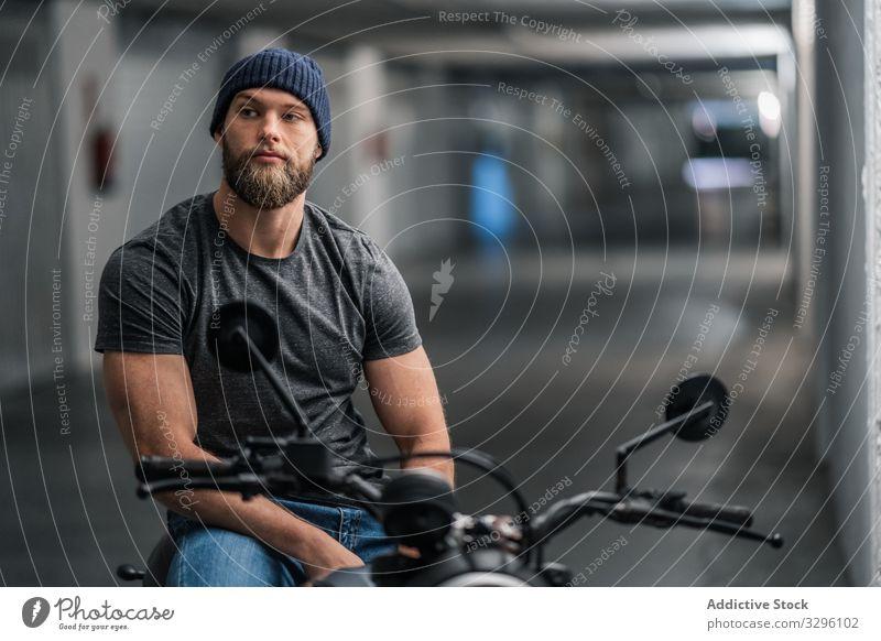 Bärtiger Biker im Garagenflur Motorrad Mann modern sitzen selbstbewusst bärtig Verkehr Mitfahrgelegenheit männlich Fahrzeug Großstadt urban Flur Gang