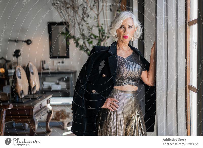 Boshafte elegante Frau gegen Vintage-Interieur im Landhaus Reichtum retro Innenbereich stylisch Mode gealtert Vorschein altehrwürdig Jacke stilvoll