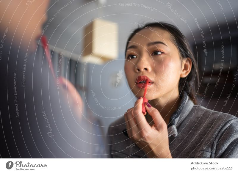 Junge Frau trägt Lippenstift vor dem Spiegel auf Make-up Kosmetik lässig bewerben Schönheit jung Reflexion & Spiegelung Gesicht Mode Pflege Teint