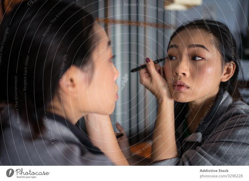 Asiatin trägt Eyeliner vor dem Spiegel auf Frau Make-up Kajal Kosmetik lässig bewerben Schönheit Auge Reflexion & Spiegelung jung Gesicht Mode Pflege Teint