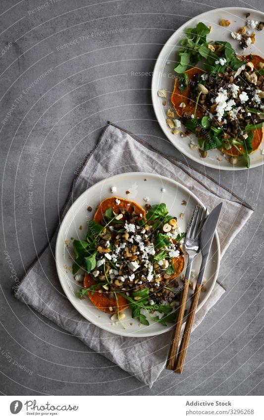 Köstlicher frischer Salat auf dem Tisch Salatbeilage Mittagessen Süßkartoffel gebacken Speise Silberwaren Teller Serviette Küche Gesundheit Lebensmittel