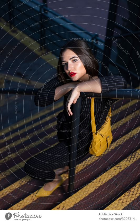 Frau in modischem Outfit mit Schirmmütze direkt an der Stadtstraße trendy Abenddämmerung Schatten stylisch Bekleidung Großstadt Straße Stehen jung