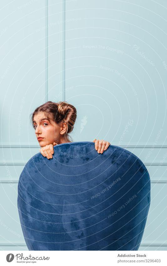 Teenager-Mädchen posiert hinter einem blauen Sessel Frau Armsessel Mode Sitzen posierend Stuhl türkis Atelier bequem Eleganz heimwärts Raum Porträt Ausdruck
