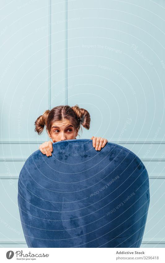 Verängstigtes Teenager-Mädchen in einem blauen Sessel furchtbar Frau Armsessel Mode Sitzen posierend Stuhl türkis Atelier bequem Eleganz heimwärts Raum Porträt
