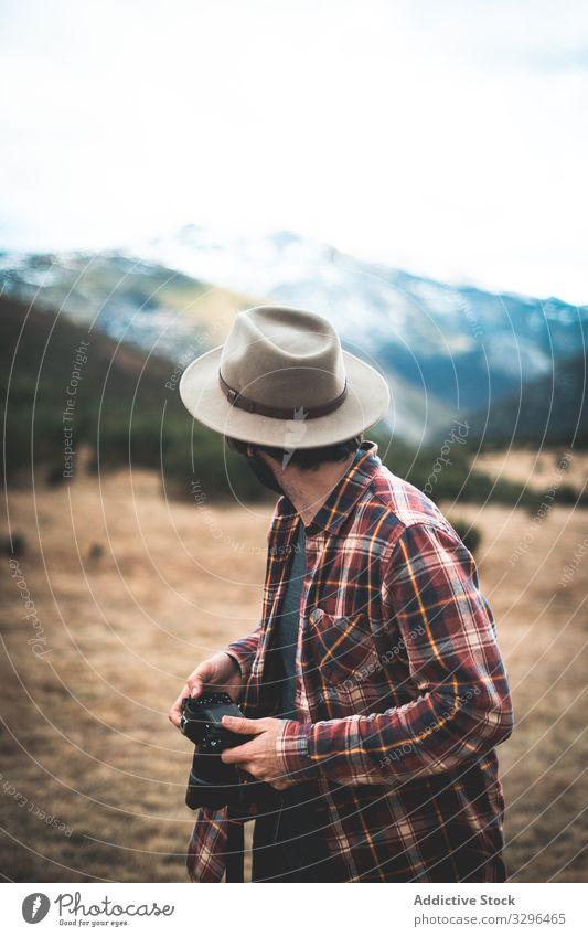 Mann mit Kamera in der Hand blickt zurück auf Berge Reisender Fotokamera Berge u. Gebirge Hut reisen Fotograf Natur Abenteuer Tourist Urlaub Fotografie Freiheit