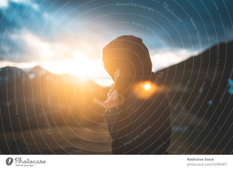 Mann in warmer Jacke mit Kapuzenpullover im Tal schaut im Sonnenlicht weg Reisender Berge u. Gebirge reisen Fotograf Natur Abenteuer Tourist Urlaub Fotografie