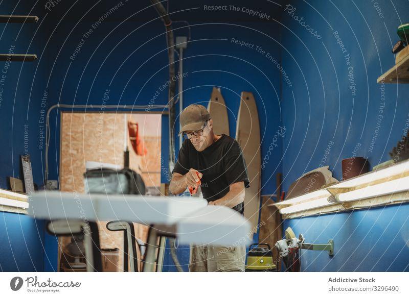 Handwerker, der ein Surfbrett ausschneidet Mann kreieren Kunstgewerbler Arbeit geschnitten Säge Kleinunternehmen Schiffsplanken Werkstatt professionell Beruf