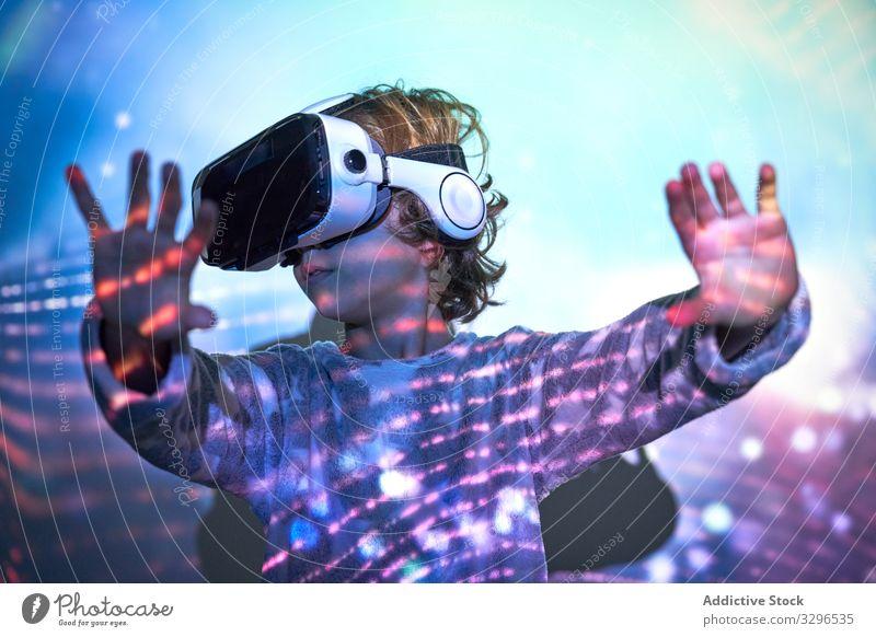 Kind trägt zu Hause eine virtuelle Brille mit Farblichteffekten Technik & Technologie Realität Freizeit Kindheit Entertainment Frau Headset Mädchen bezaubernd