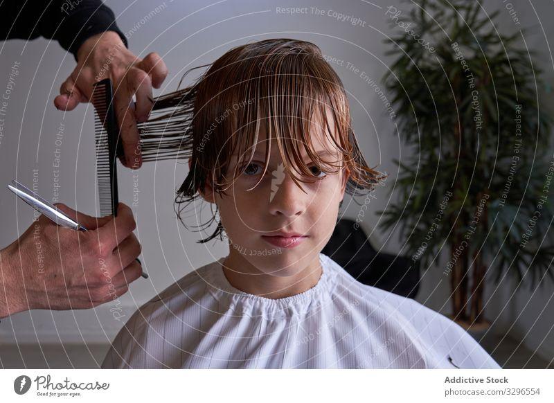 Junge schneidet seine Haare beim Friseur geschnitten Barbershop Kind jung Behaarung Mode Salon Frisur Trimmen Frau Haarschnitt Sitzen Schönheit beliebt Stuhl