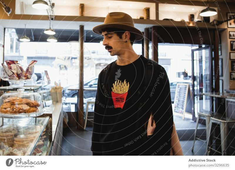 Hipster betrachtet Desserts im Schaufenster einer Bäckerei Mann Aussehen Sortiment Wahl Gebäck Frankreich Paris Anzeige sich[Akk] entspannen männlich Erholung