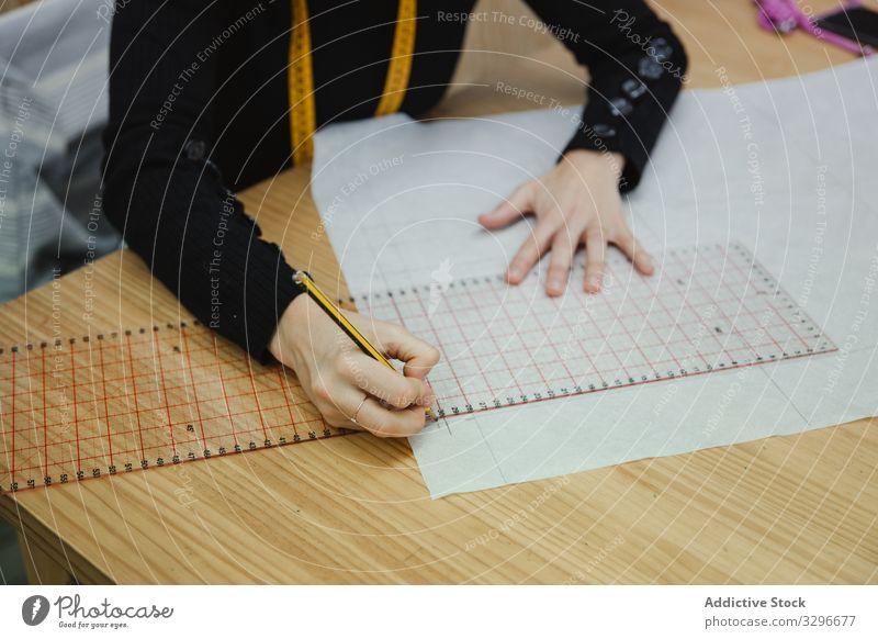 Schneiderinnen-Zeichnungsausschnitt in der Werkstatt zeichnen Ausschnitt Frau Tisch fokussiert Arbeit Erwachsener Designer Arbeitsplatz professionell