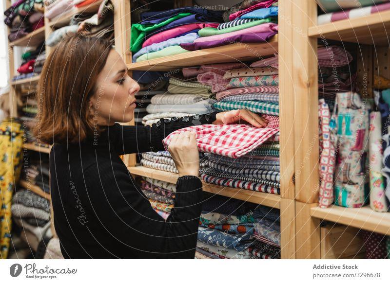 Schneiderin bei der Stoffauswahl im Lagerraum Gewebe wählen Regal Werkstatt Frau stöbern Beruf Designer professionell Mode Erwachsener Job Atelier Probe