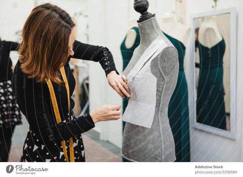 Schneiderin arbeitet mit Schaufensterpuppe im Atelier Damenschneiderin Werkstatt Frau befestigen Ausschnitt Stecknadel Bekleidung Designer Mode Beruf Handwerk