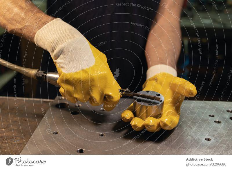 Gesichtsloser Vorarbeiter benutzt Ausrüstung in der Werkstatt Polier benutzend Gerät Mann Handschuhe prüfen vorbereiten Sicherheit Industrie Schutz männlich