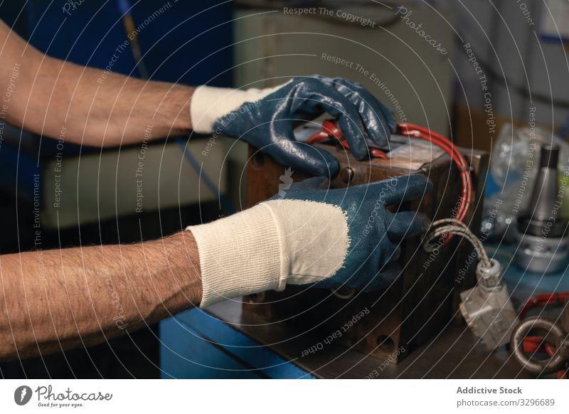 Mechanismus zum Zusammenbau der Erntehelfer in der Werkstatt Mann versammeln Maschine Hobelbank Handschuh Handwerk Industrie Arbeit Reparatur männlich