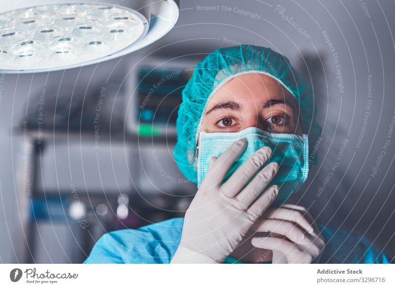 Weibliche Chirurgin im Operationssaal Krankenhaus Mundschutz Hut bereit Frau Arbeit Arzt Gesundheitswesen Job Uniform Medizin Kompetenz professionell Gerät