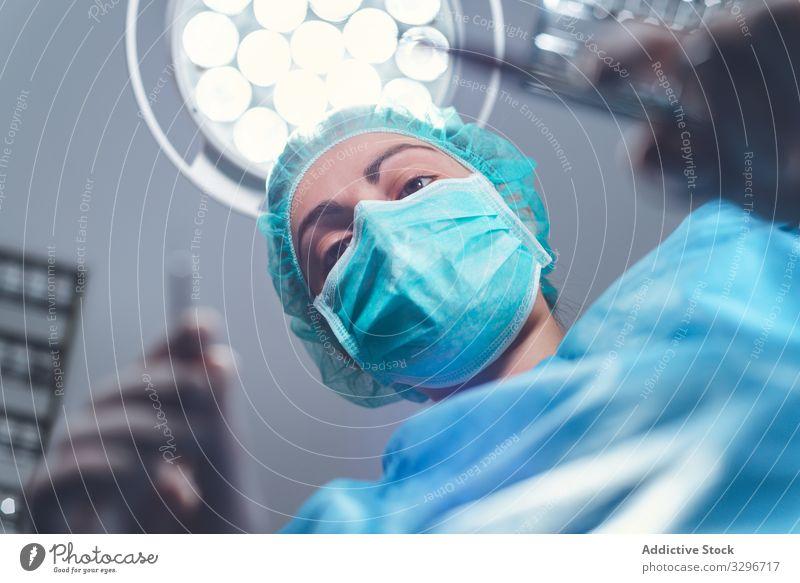 Frau, die im Krankenhaus operiert Chirurg Operationssaal Lampe Werkzeug Mundschutz Hut Arbeit Arzt Gesundheitswesen steril Instrument Job Uniform Medizin