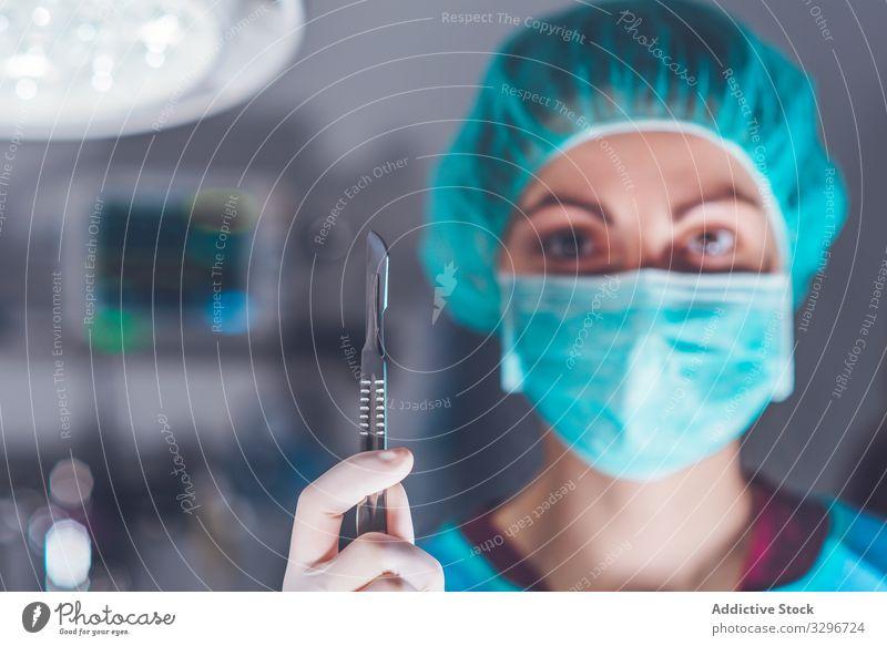 Weibliche Chirurgin im Operationssaal Krankenhaus Skalpell Mundschutz Hut bereit Frau Arbeit Arzt Gesundheitswesen stechend Lanzette steril Messer Werkzeug