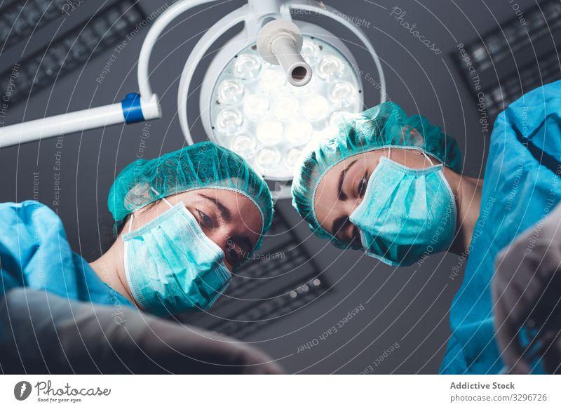 Frauen, die gemeinsam im Krankenhaus operieren Chirurg Operationssaal Lampe Werkzeug Mundschutz Hut Arbeit Arzt Gesundheitswesen steril Instrument Zusammensein