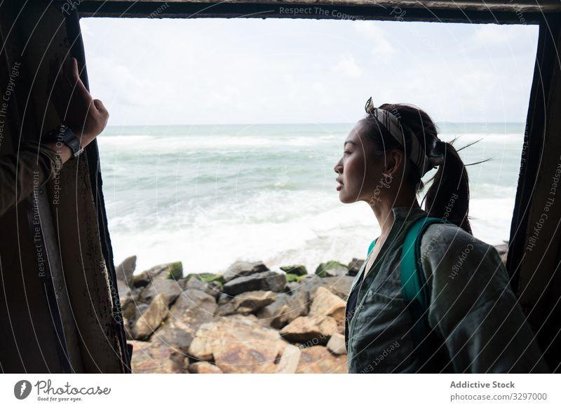 Neugierige Frau im Urlaub mit dem Küstenzug unterwegs reisen Zug Verkehr Küstenstreifen Meeresufer neugierig Türöffnung Ansicht Strand Seeküste Ausflugsziel