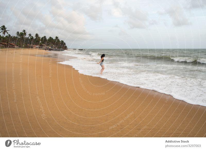 Anonyme friedliche Frau an einsamer Küste Tourismus Meeresufer reisen Strand laufen leer Sand erkunden Ansicht Himmel Cloud winken negombo Sri Lanka Küstenlinie