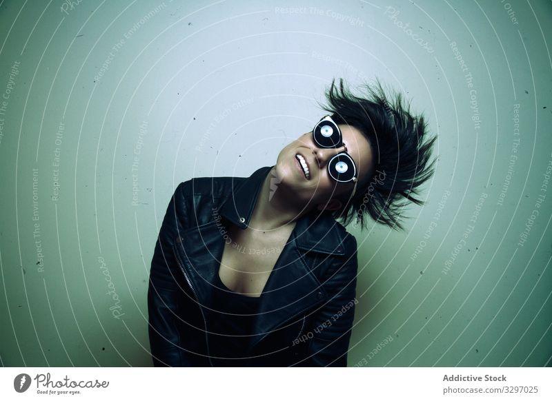Starke junge Rockerin in Lederjacke im Studio Frau Sonnenbrille Model Schönheit Felsen Punk Atelier schwarz Frisur Porträt Biker Grunge Person modisch hart