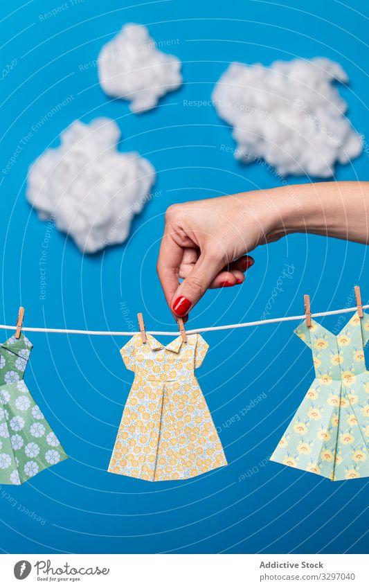 Nutzpflanzenfrau befestigt Origami-Kleider am Seil Frau Konzept befestigen hängen Sauberkeit Wäscherei Himmel Cloud hell lebhaft pulsierend Papier Attrappe