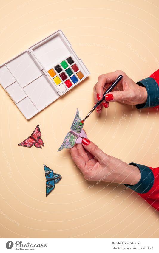 Getreidefrau malt Papier-Schmetterlinge Frau Origami Farbe Konzept Kunst Wasserfarbe Ornament kreativ Bürste Insekt Wanze Flügel Dekor Design vorsichtig