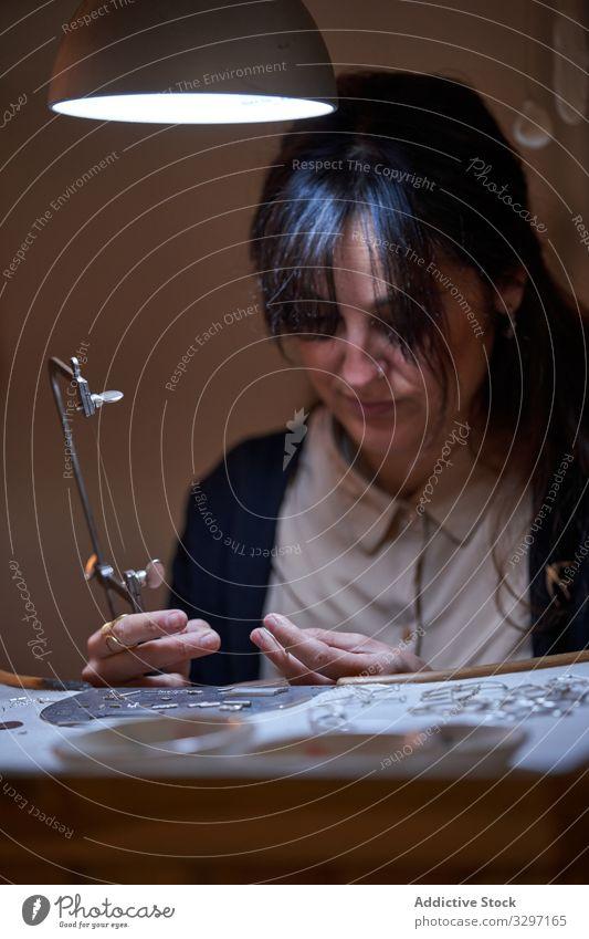 Frau, die in einem Juweliergeschäft arbeitet gold Kunsthandwerker Metall Accessoire Goldschmied Lupe Schmuck Ring Handwerk Arbeit Herstellung Werkstatt manuell