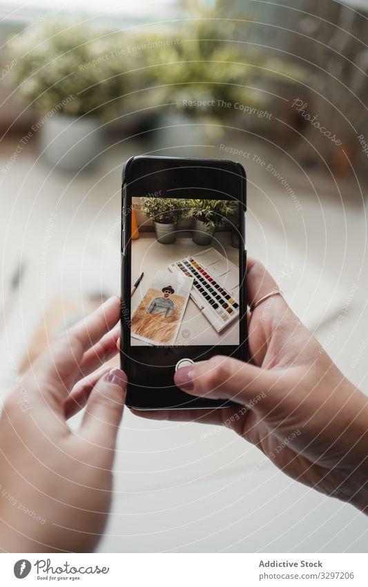 Nicht erkennbare Malerin fotografiert auf Smartphone am Arbeitsplatz Anstreicher fotografierend Zeichnung Frau Werkstatt Wasserfarbe Funktelefon Skizze Job