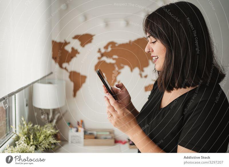 Fokussierte Frau mit dunklen Haaren, die Nachrichten über Mobiltelefone verschickt, während sie sich in der Nähe eines Desktop-Computers im Büro in Paris aufhält