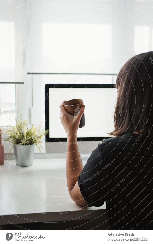 Anonyme Frau, die am Arbeitsplatz mit einem Smartphone fotografiert fotografierend Bild Arbeitsbereich Funktelefon Büro Computer benutzend Tasse teilen