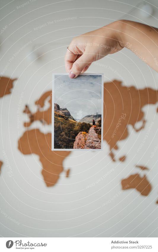 Anonyme Frau hält Bild vor der Weltkarte Postkarte Foto weltweit Information reisen Lifestyle Reise Planet Erde Objekt Geografie Land Tourismus senden