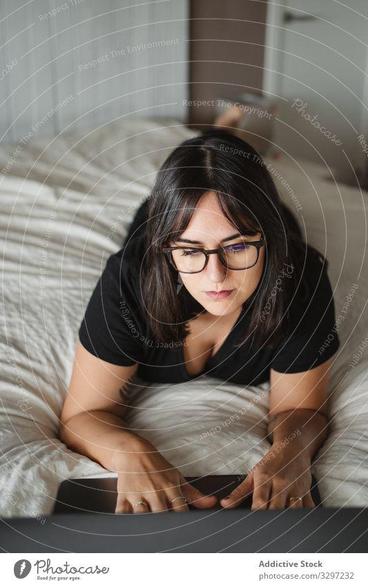 Fokussierte junge Studentin benutzt Laptop am Bett zu Hause Schüler benutzend Frau Tippen lernen Lügen Bildung Mitteilung Anschluss Kontakt Internet online
