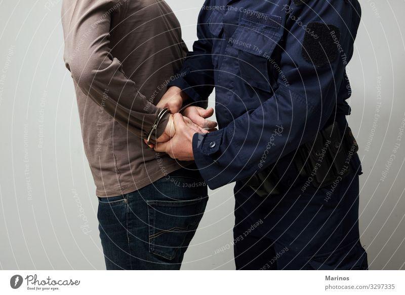 Polizist in Handschellen mit einem Illegalen. Mensch Mann Erwachsene Sicherheit Schutz Geborgenheit Gewalt Schuld Verbrechen Krimineller