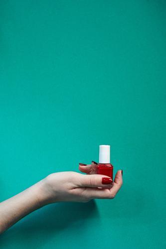 Rote Polierflasche in Frauenhand. Flasche schön Maniküre Behandlung Spa Mensch Erwachsene Hand Finger rot Farbe nageln Pflege Salon Trimmen Beautyfotografie