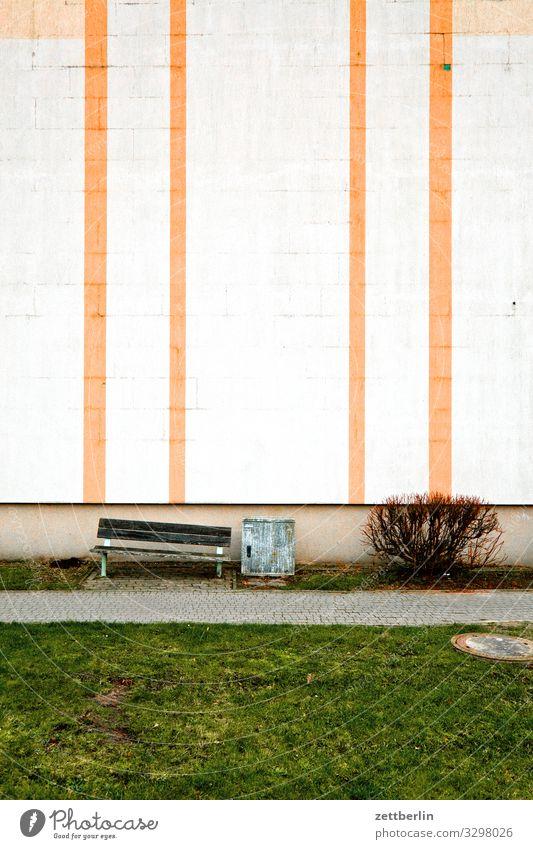 Fassade mit Streifen Haus Mehrfamilienhaus Wohnhaus Plattenbau wbs 70 Neubausiedlung Wand Mauer Bank Menschenleer Textfreiraum trist Traurigkeit Einsamkeit