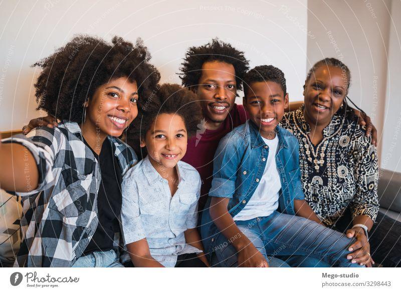 Mehrgenerationen-Familie, die sich zu Hause selbstständig macht. Lifestyle Freude Glück Leben Sofa Kind Telefon Mensch Frau Erwachsene Eltern Mutter Vater