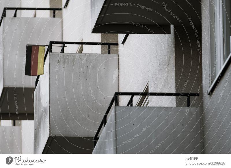trostlose Balkone aus Beton mit kleiner Deutschlandfahne Stadt Haus Hochhaus Bauwerk Fassade Fahne Armut bedrohlich dunkel kalt modern Klischee trist