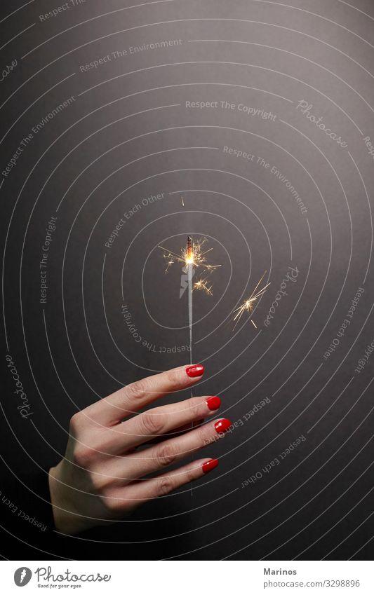 Wunderkerze in Frauenhand mit rotem Nagellack schön Maniküre Spa Dekoration & Verzierung Feste & Feiern Erwachsene Hand Finger hell Farbe nageln Pflege Salon