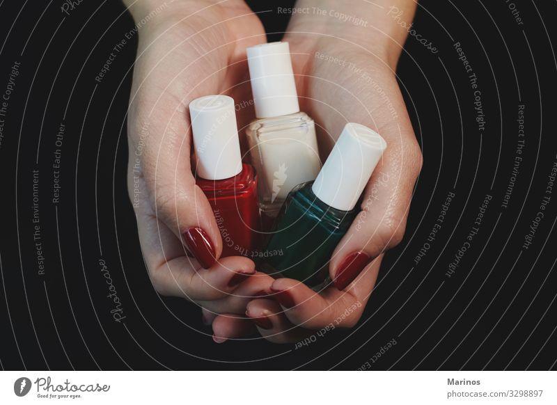 Polnische Flaschen in Frauenhänden. schön Maniküre Behandlung Spa Mensch Erwachsene Hand Finger rot Farbe nageln Pflege Salon Trimmen Beautyfotografie Nägel