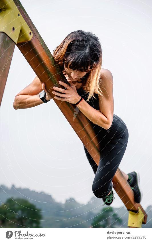 Sportlerin beim Training an eine Holzstange gepackt Lifestyle Körper Klettern Bergsteigen Mensch Frau Erwachsene Natur Park Fitness dünn muskulös stark Kraft
