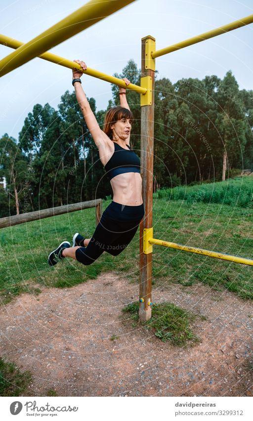 Sportlerin bei Klimmzugübungen Lifestyle Körper Mensch Frau Erwachsene Arme Natur Park Turnschuh Fitness dünn stark Kraft anstrengen Energie